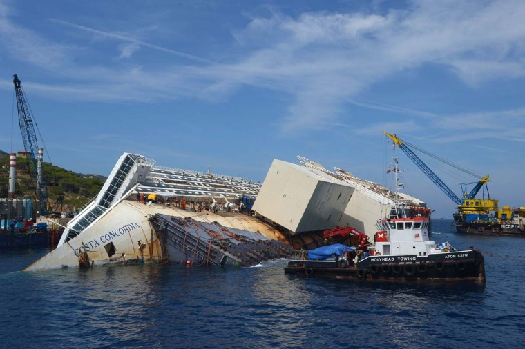 Salvage workers prepare the Costa Concordia cruise ship at Goglio Island. The Costa Concordia will be raised up in September near the Italian island where it still lies after a disaster on Jan. 13, 2012. (Vincenzo Pinto / AFP/Getty Images)