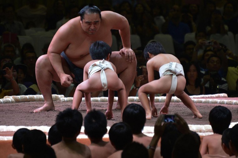 A Japanese sumo teacher is seen in a mock fight with two children during an exhibition before a two-day sumo tournament in Jakarta on August 24, 2013. The sumo world tour in Jakarta will be the opening event, and the first one since the Mongol Tour in August 2008, with the tournament marking the 55th year of diplomatic relation between Indonesia and Japan. (Bay Ismoyo/AFP/Getty Images)
