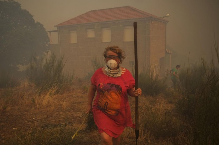 A woman with a mask tries to help at the site of a wildfire in Sandin, near Ourense in Spain on August 24, 2013. (Pedro Armestre/AFP/Getty Images)