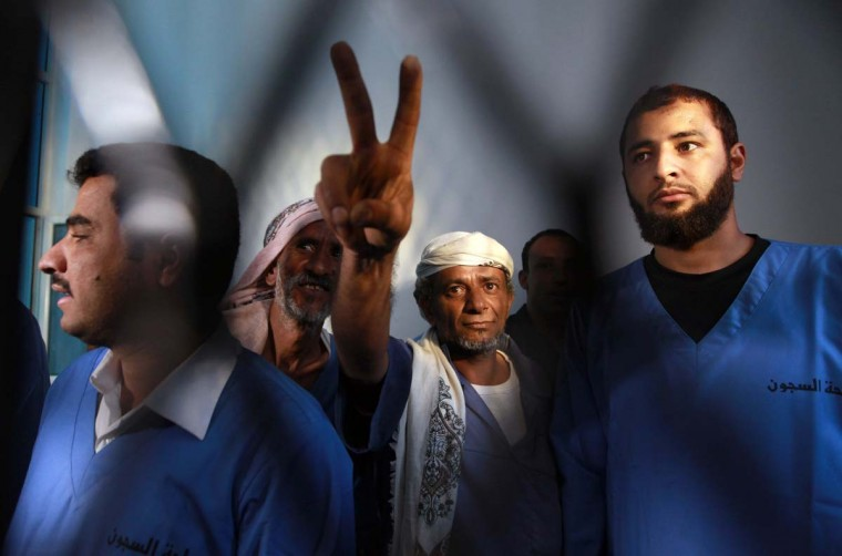 Defendants stand behind metal bars during the first hearing on August 26, 2013 in the case of the June 2011 bombing of the Yemeni presidential palace at the state security court in Sanaa. Former Yemeni president Ali Abdullah Saleh was wounded in a explosion in the presidential compound that killed 11 others on June 3, 2011. (Huwais Mohammed/AFP)