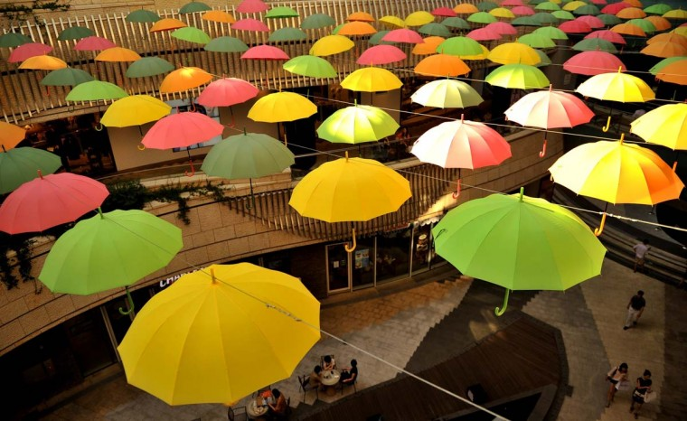 People walk through a mall where umbrellas are displayed in Seoul on August 26, 2013. South Korea's jobless rate was unchanged at 3.2 percent in July, Statistics Korea said on August 14, after new employment openings in education and social services offset losses in the manufacturing sector. (Lee M. Truth/AFP)