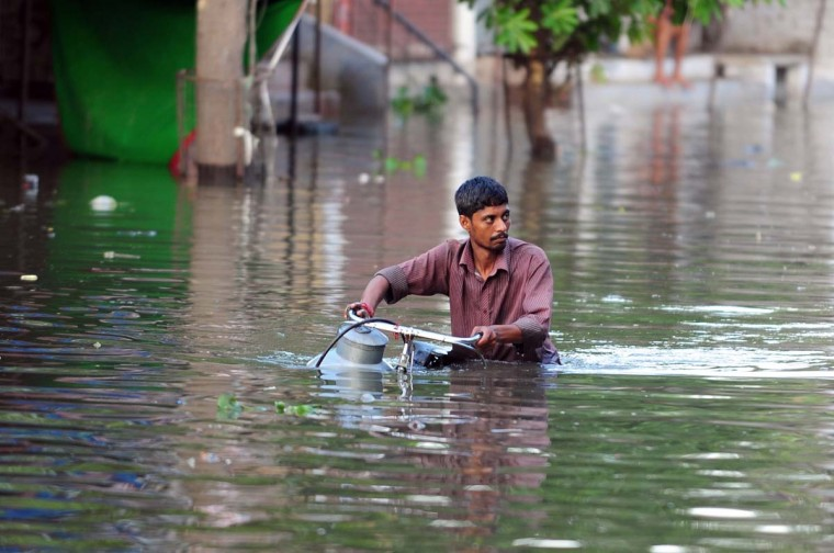 An Indian resident wades through a road with flooded water from the river Ganga in Allahabad on August 26, 2013. With the major rivers in Uttar Pradesh flowing above the red mark, several districts in the state, including Allahabad and Gorakhpur were affected by the rising water level, resulting into floods in a number of inhabited areas. (Sanjay Kanojia/AFP)