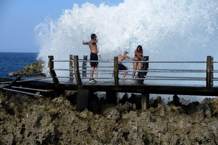 Foreign tourists enjoy water hitting the shore at a beach in the Nusa Dua resort island in Bali on August 27, 2013. US President Barack Obama will join other leaders at the 21-member Asia-Pacific Economic Cooperation (APEC) summit held in Nusa Dua in early October 2013. (Sonny Tumbelaka/AFP/Getty Images)