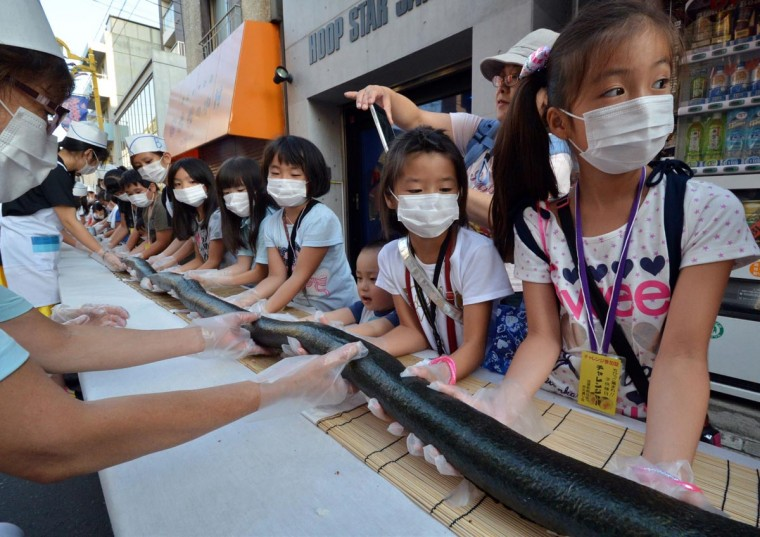 Children and volunteers help make a 393 feet roll sushi to serve local people at an annual summer festival in Tokyo on August 27, 2013. (Yoshikazu Tsunoyo/AFP/Getty Images)