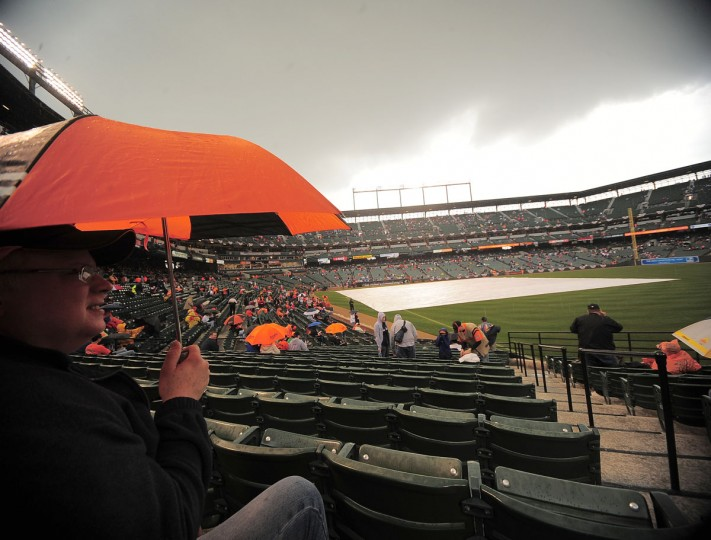 While you're keeping dry: David Evans of Pasadena, Md., takes shelter under an umbrella as rain falls on Oriole Park at Camden Yards during an Opening Day game on April 6, 2009. (Karl Merton Ferron/Baltimore Sun Photo)