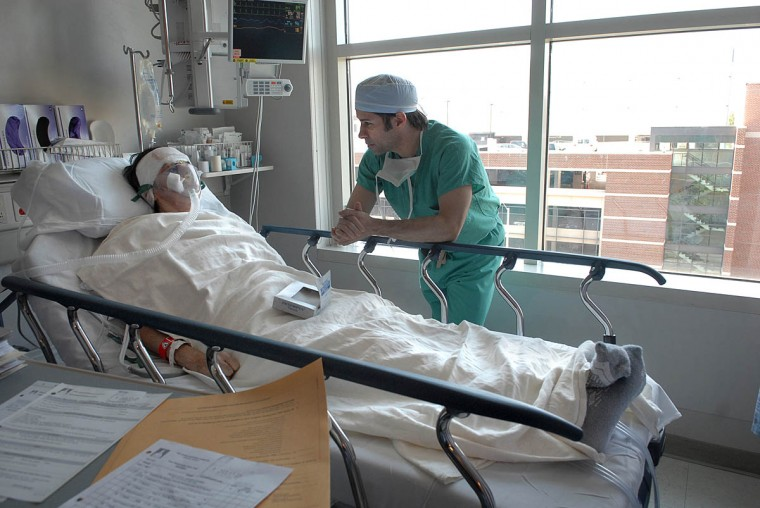"""Dr. Patrick Byrne visits Linda Hershey after surgery. In describing nasal reconstruction, Byrne said that there's no textbook answer. """"We know the techniques. But which technique to choose and when and why depending on the particular patient's situation is really difficult to call."""" (Algerina Perna/Baltimore Sun/July 15, 2008)"""