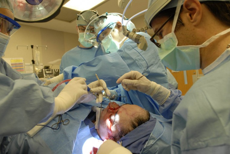 In the second major nose reconstruction operation lasting ten hours, Dr. Patrick Byrne and his team harvest Linda Hershey's rib and ear cartilage, then graft them onto her nose (Algerina Perna/Baltimore Sun/June 17, 2008)