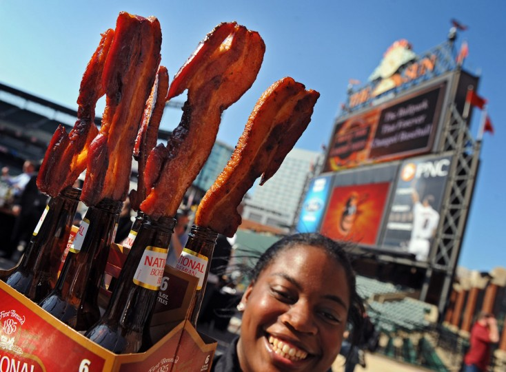 While you're working: Orioles server Jasmie Mitchell shows off the Bacon on a Stick at Oriole Park at Camden Yards in April 2012. (Kenneth K. Lam/Baltimore Sun Photo)
