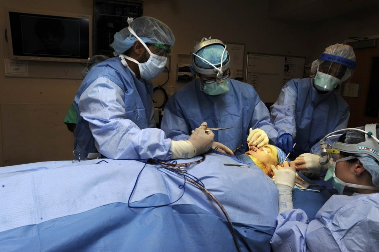 "Surgeons place cadaver rib cartilage inside Linda Hershey's nose. Dr. Patrick Byrne, second from left, places places an implant ""to help lift the [right] eye to a more normal position,"" he explains. (Algerina Perna/Baltimore Sun/Sept. 28, 2010)"
