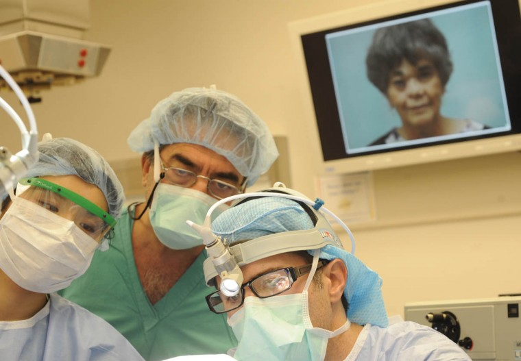 Dr. Patrick Byrne, right, places cadaver rib cartilage into Linda Hershey's new nose. In the center is Theodoros Papadas, MD, a visiting surgeon from Greece. In the background is a projection of Hershey's face. (Algerina Perna/Baltimore Sun/Sept. 28, 2010)