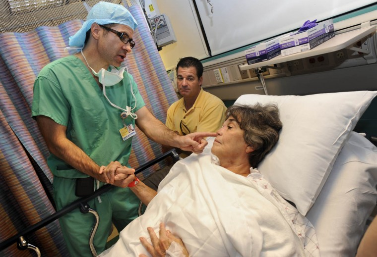 Dr. Patrick Byrne speaks to Linda Hershey before performing a donor graft operation on her nose. After her rib cartilage graft dissolved from a surgery over two years ago, Hershey and Byrne decided to use cadaver cartilage to give a better shape to her nose. In the background is Hershey's son, Scott Rogers, 41. (Algerina Perna/Baltimore Sun/Sept. 28, 2010)