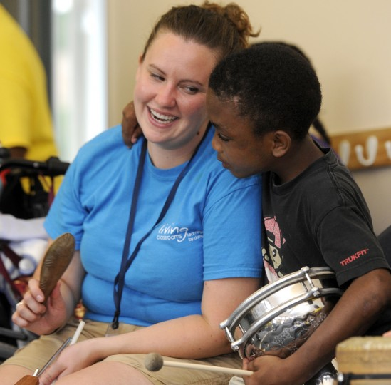Rachael Dickey, left, an educator with the Living Classrooms Foundation, plays a drum with Ty'Jay House, 9, a student from the William S. Baer School who is participating in The Arc Baltimore's Bay Buddies summer camp program. (Barbara Haddock Taylor/Baltimore Sun)