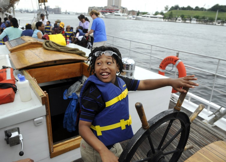 Taylan Bonds, 7, a student from the William S. Baer School in Baltimore smiles as he steers the skipjack Sigsbee on a cruise around the Inner Harbor. The ship is part of the Living Classrooms Foundation. (Barbara Haddock Taylor/Baltimore Sun)
