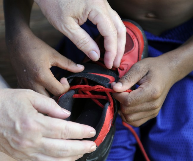 A teacher helps a student learn to tie his shoe. Students from the William S. Baer School who are participating in The Arc Baltimore's Bay Buddies summer camp enjoy a day at the Druid Hill Park pool. (Barbara Haddock Taylor/Baltimore Sun)