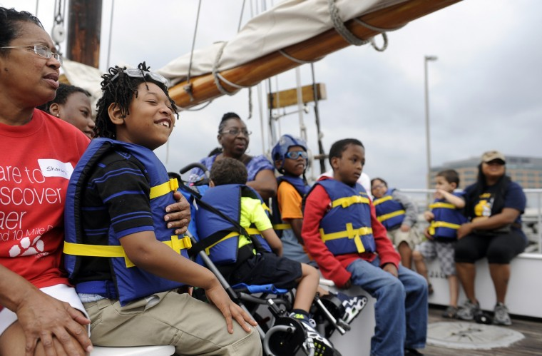 Sharon Maddox, left, a paraeducator, holds Taylan Bonds, 7. He is one of several students from the William S. Baer School in Baltimore who enjoyed a ride aboard the skipjack Sigsbee, which is part of the Living Clasrooms Foundation. The children are participating in the Bay Buddies summer camp program, which is sponsored by The Arc Baltimore. (Barbara Haddock Taylor/Baltimore Sun)