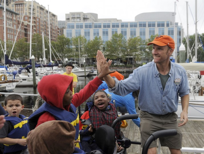 Ty'Jay House, 9, left, high-fives Peter Bolster, captain of the skipjack Sigsbee, after he and other students enjoyed a ride aboard the ship. The children are participating in the Bay Buddies summer camp. (Barbara Haddock Taylor/Baltimore Sun)