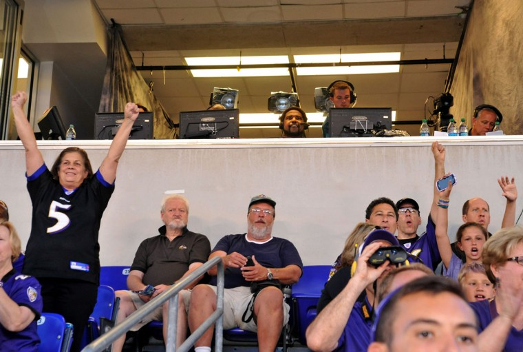 Ravens fans cheer in the stands below the broadcast booth, where Hall of Famer Jonathan Ogden (center) joined the WBAL-TV/radio team. (Amy Davis/Baltimore Sun Photo)