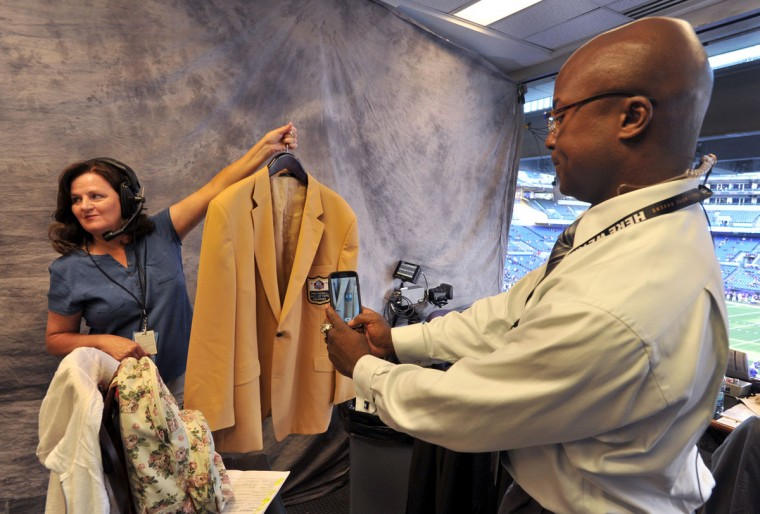 Qadry Ismail takes a photo of Jonathan Ogden's Pro Football Hall of Fame jacket, held by stage manager Karen LaGrasta. Ogden, who was inducted into the Hall of Fame earlier this month, joined the WBAL-TV/radio trio in the booth for the game. (Amy Davis/Baltimore Sun Photo)
