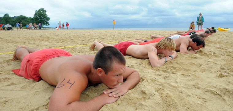 Michael Berna (#64), a lifeguard at Gunpowder Falls State Park, picks a stick that lands him on one end of the pack during a heat in the Australian Sprint Elimination (beach flags) competition. In this race the competitors start out lying belly down and face the opposite direction from which they'll run. (Algerina Perna/Baltimore Sun)