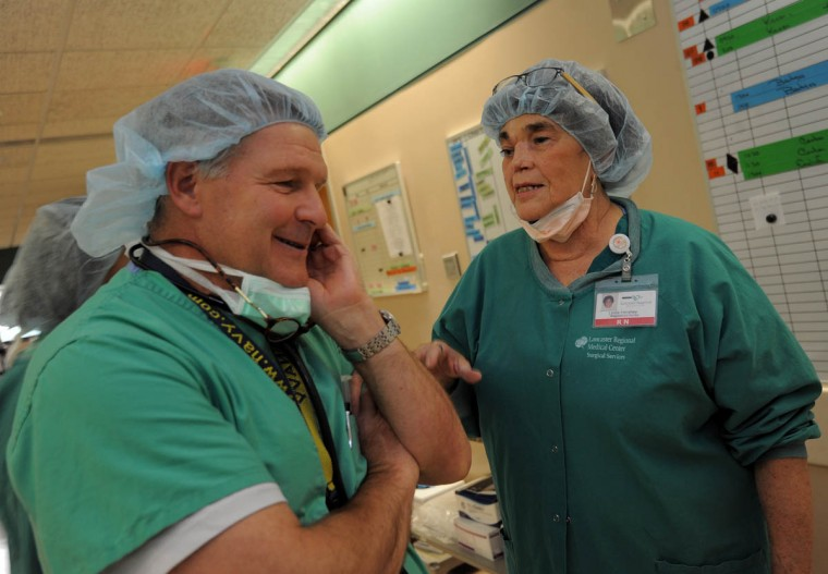 "At Lancaster Regional Medical Center, Linda Hershey, RN, chats with chief anesthesiologist, J. Eric Greensmith where Hershey is an OR nurse. Goldsmith who's known Linda since the '80s, says, ""I've never seen her flag in her spirit. She just keeps going. She's got just a great manner with the patients."" (Algerina Perna/Baltimore Sun/June 6, 2013)"