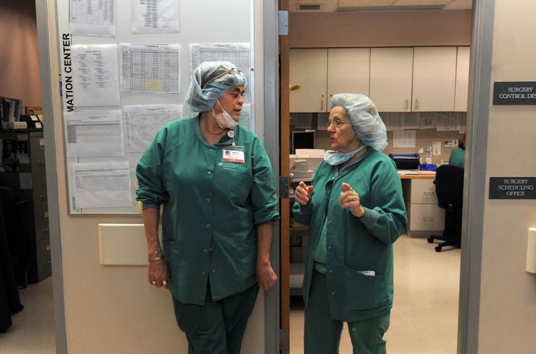 Linda Hershey, left, is pictured at her job as an OR nurse at Lancaster Regional Medical Center speaking with Sandy Gladfelter, charge nurse and friend, who's driven Hershey to Johns Hopkins several times for her surgeries and procedures scheduling facilitator. (Algerina Perna/Baltimore Sun/June 6, 2013)