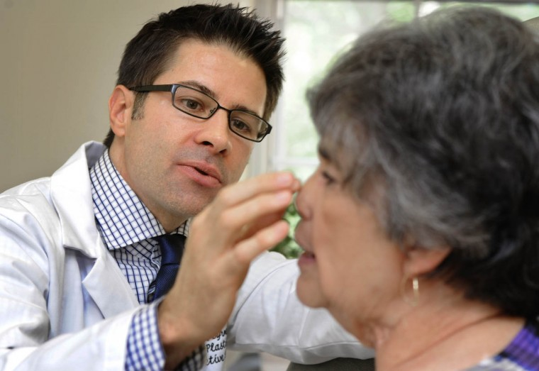 "Dr. Patrick J. Byrne, director, Johns Hopkins division of facial plastic and reconstructive surgery, examines Linda Hershey's nose during an office visit. Just over one and a half years after her nose removal, Hershey says, ""I can't say enough good things about my doctor...how impressed I am with the kind of human being he is deep down as well as the talents he holds.... I have never worked with a plastic surgeon like him - ever."" (Algerina Perna/Baltimore Sun/Aug. 5, 2010)"