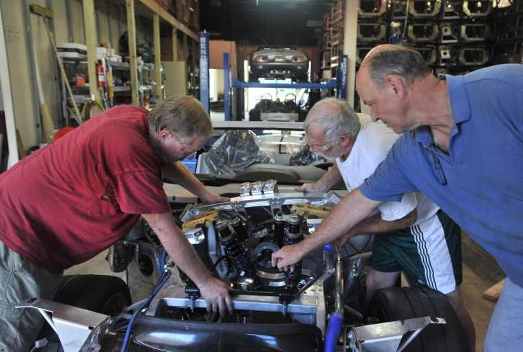 Randy Hubbert, left, Steve Pranger, center, and Bob Wingard work on the suspension removal process of a rare Series 1 car. (Gene Sweeney, Jr./Baltimore Sun)