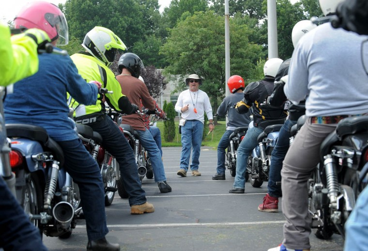 "Chris Pollard, center, one of the motorcycle program faculty, gives students instructions before they ride. Students in the Rider School practice on the motorcycle instructional ""south range"" near the athletic building at Howard Community College. (Algerina Perna/Baltimore Sun)"