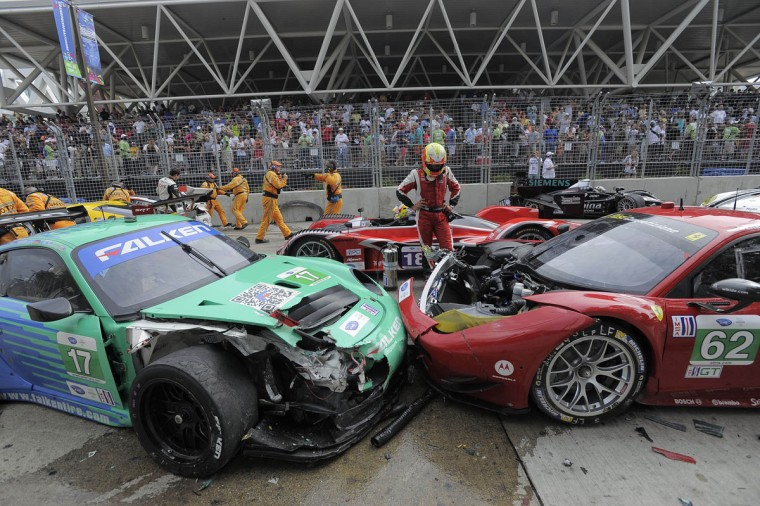 A driver stands looking at the wreckage in front of the Baltimore Convention Center grandstand at the start of the ALMS Series Race. (Karl Merton Ferron / Baltimore Sun Staff)