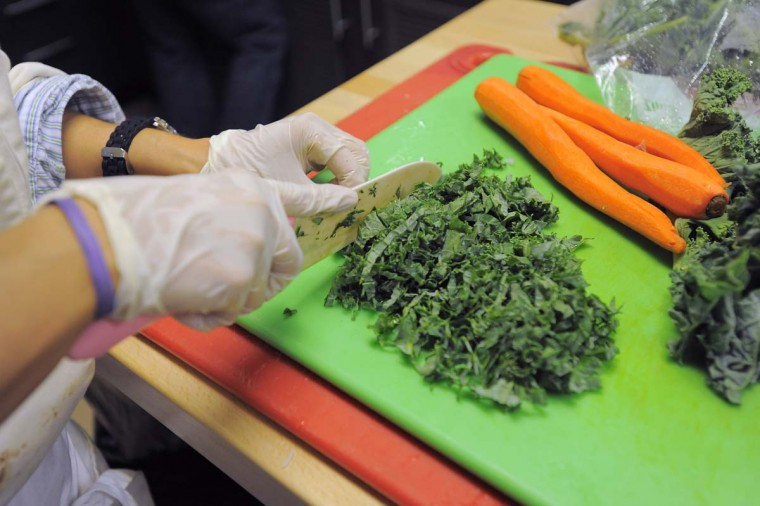 """Orioles chef Jenny Perez chops kale that she purchased at a local farmers' market. """"If they want hot dogs, they're going to have hot dogs,"""" says vice president Brady Anderson. """"But the opportunity to eat well is here, and that's what's important."""" (Karl Merton Ferron/Baltimore Sun Photo)"""