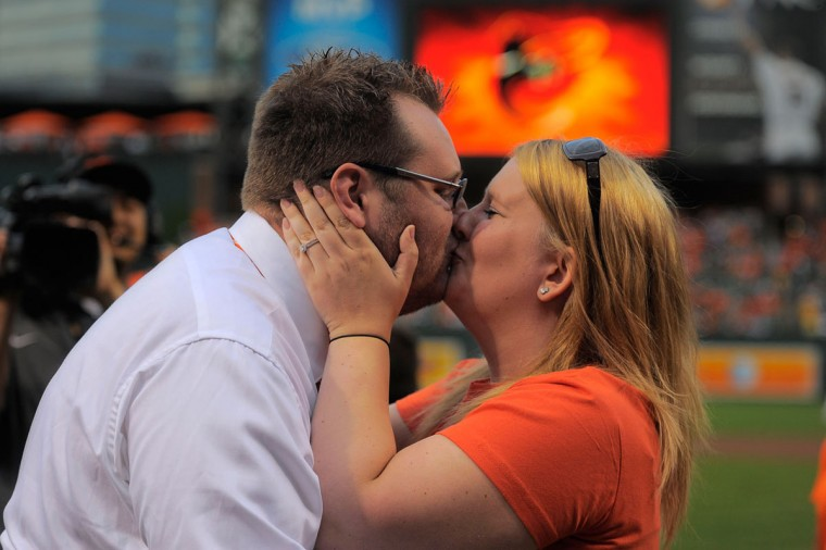 National anthem singer Michael Fries (left) gets a kiss from Shelby Trautman after she accepted his on-field marriage proposal Saturday night at Camden Yards (Karl Merton Ferron/Baltimore Sun Photo)