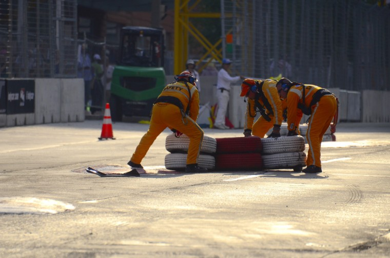 A track crew pulls tires back behind a chicane after it was hit by a race car during the 2013 Grand Prix of Baltimore Friday, Aug. 30, 2013. (Karl Merton Ferron/Baltimore Sun)