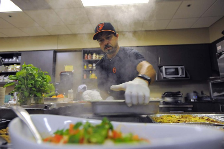 Carlos Cruz places a tray of steamed rice on the Orioles' clubhouse buffet counter. (Karl Merton Ferron/Baltimore Sun Photo)