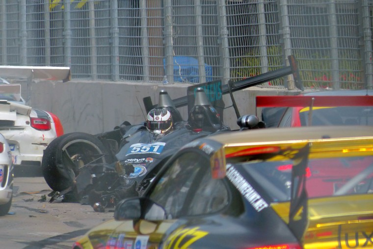 The No. 551 car smokes as other cars avoid him after he hit the retaining wall at the scene of the major crash involving numerous race cars on the main straightaway on Pratt Street at the start of the ALMS Series Race. (Karl Merton Ferron / Baltimore Sun Staff)