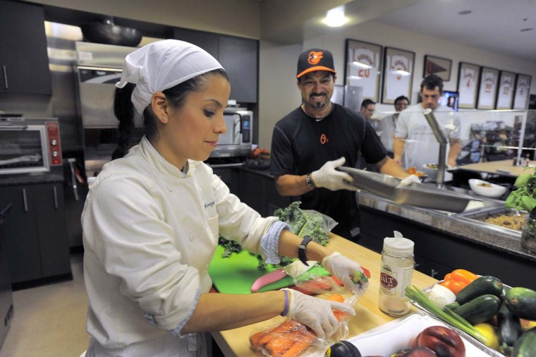 """Jenny Perez (left) and Carlos Cruz prepare food for the Orioles in the clubhouse kitchen. """"See how green and nice and ripe everything is,"""" said first baseman Chris Davis. """"It's made by real humans."""" (Karl Merton Ferron/Baltimore Sun Photo)"""