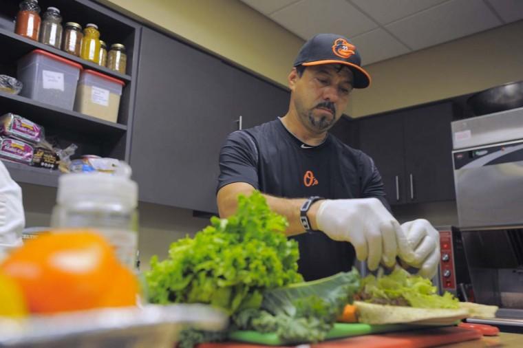 Carlos Cruz prepares a burrito for third baseman Manny Machado in the clubhouse kitchen. (Karl Merton Ferron/Baltimore Sun Photo)