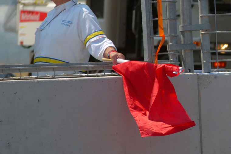 A red flag is waved following a crash at IZOD IndyCar qualifying race during the 2013 Grand Prix of Baltimore. (Karl Merton Ferron/Baltimore Sun Photo)