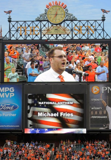 Michael Fries is shown on the scoreboard singing the national anthem before proposing to his girlfriend, Shelby Trautman, on Saturday night at Camden Yards. (Karl Merton Ferron/Baltimore Sun Photo)