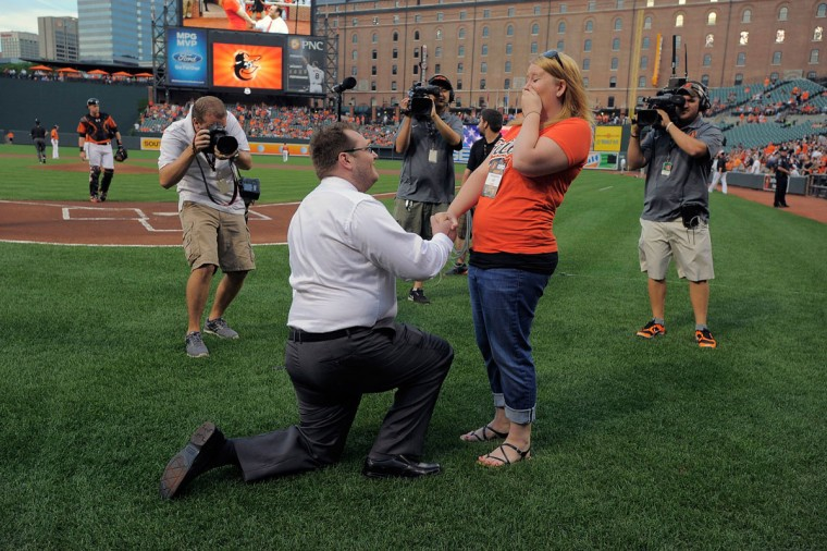 Michael Fries (left) proposes to his girlfriend, Shelby Trautman, after singing the Star-Spangled Banner on Saturday night at Camden Yards. (Karl Merton Ferron/Baltimore Sun Photo)
