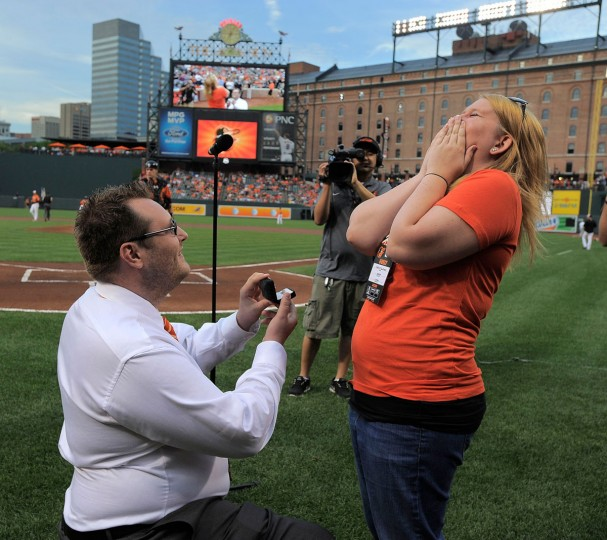 "Michael Fries (left) proposes to his girlfriend, Shelby Trautman, after singing the Star-Spangled Banner on Saturday at Camden Yards. Trautman said ""yes."" (Karl Merton Ferron/Baltimore Sun Photo)"
