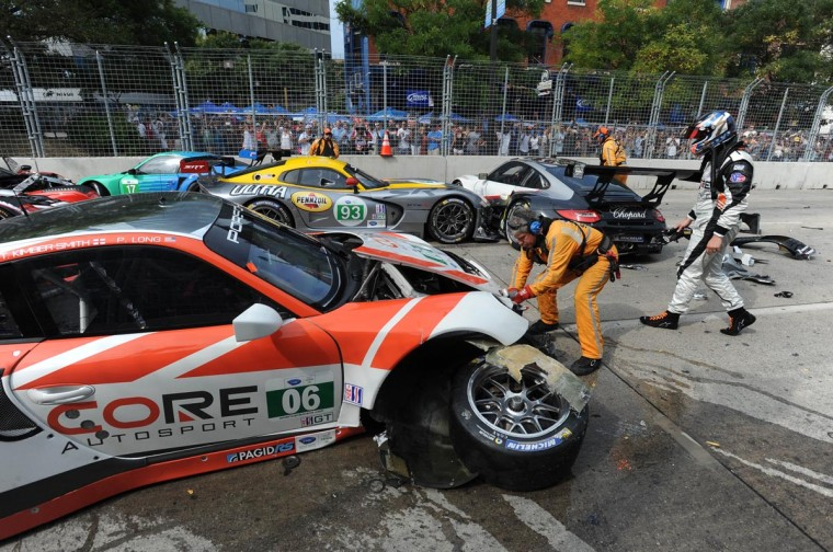 Safely crew members begin untangling the wreckage after a massive pileup at the start of the ALMS race. (Jerry Jackson/Baltimore Sun)