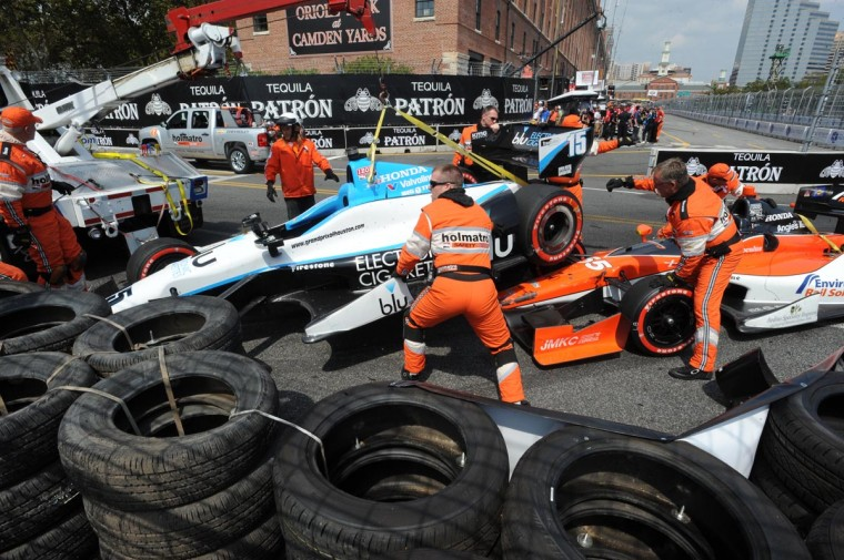 Track crewmembers remove the damaged cars of Graham Rahal and Tristan Vautier after an accident in turn 8 during IndyCar qualifying.(Jerry Jackson/Baltimore Sun)