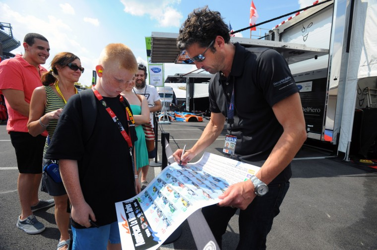 Actor and race car driver Patrick Dempsey, right, signs autograph for Zachary Barnickel, 11, of Essex, at the paddock. Dempsey is promoting a fund raising for the Patrick Dempsey Center for Cancer Hope & Healing. He will be racing in Saturday's ALMS GT race of the Baltimore Grand Prix. (Kenneth K. Lam/Baltimore Sun)