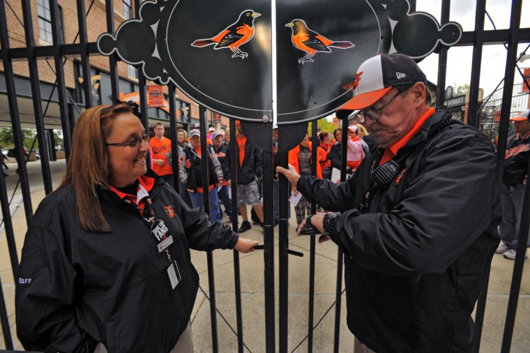 Through a gate: Ticket scanner Lisa Griffin looks at Corell Turck, who makes sure to open the Eutaw Street gate at 4 p.m. as fans wait in line for an American League Divisional Series game Orioles and the Yankees at Oriole Park at Camden Yards, Oct 7, 2012. (Karl Merton Ferron/Baltimore Sun Photo)
