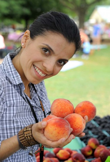 Chef Jenny Perez looks over peaches during a farmers' market shopping trip for the Orioles. (Lloyd Fox/Baltimore Sun Photo)