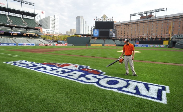 In the postseason: Sam King, a member of the Orioles grounds crew, dries the painted MLB postseason logo on the field at Oriole Park at Camden Yards in preparation for the 2012 American League Divisional Series. The O's faced the Yankees in their first postseason appearance in 15 years. (Lloyd Fox/Baltimore Sun Photo)