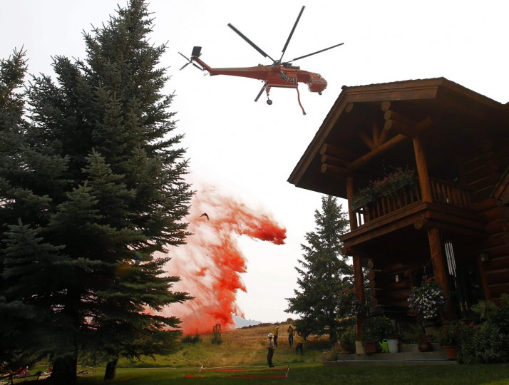A helicopter tanker drops fire retardant near a home at the Beaver Creek wildfire outside Ketchum, Idaho August 18, 2013. Firefighters readied for a massive ground and air attack on Sunday against a wildfire in central Idaho that has forced the evacuation of some 2,250 homes and threatens the posh Sun Valley ski resort. (Jim Urquhart/Reuters)