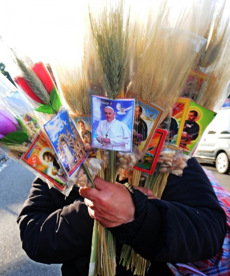 A peddler sells souvenirs with images of Pope Francis and Saint Cayetano as people queue at the Sanctuary of Saint Cayetano -- Argentina's patron saint of bread and work -- in Liniers, a neighbourhood in western Buenos Aires where thousands of faithfuls gathered to listen a prerecorded message of Pope Francis. Before becoming Pope and when he was archbishop of Buenos Aires, cardinal Jorge Bergoglio officiated the central mass at the sanctuary on Saint Cayetano feast day. (Daniel Garcia/Getty Images)