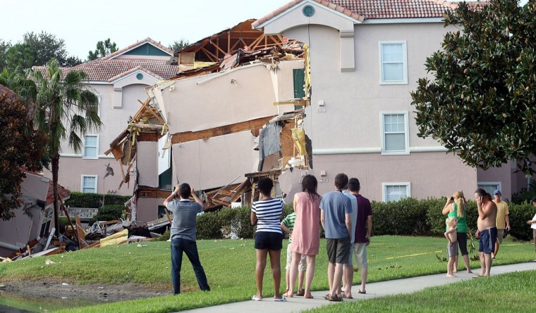 People take pictures Monday, August 12, 2013 after a sinkhole swallowed two building at Summer Bay Resort in Orlando, Florida late Sunday night. (Red Huber/Orlando Sentinel/MCT)