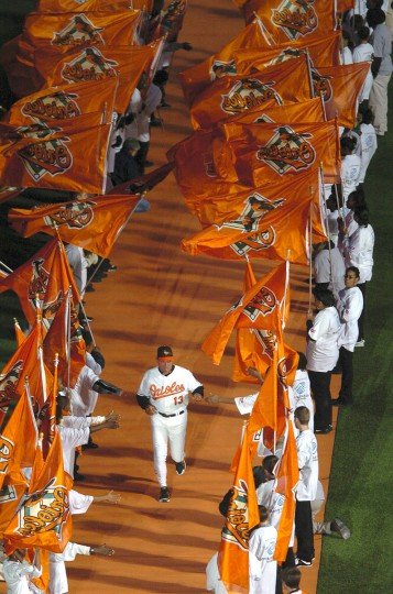 Surrounded by orange: New Orioles manager Lee Mazzili makes his way onto the field as he is introduced during Opening Day ceremonies in 2004 at Oriole Park at Camden Yards. (Lloyd Fox/Baltimore Sun Photo)